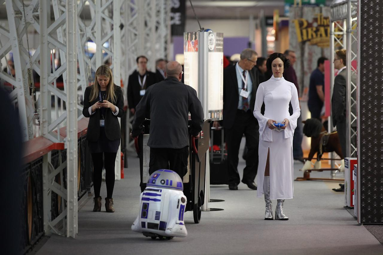 LONDON, ENGLAND - JANUARY 24:  A woman dressed as the Star Wars character Princess Leia drives a radio controlled R2D2 at the 2012 London Toy Fair at Olympia Exhibition Centre on January 24, 2012 in London, England. The annual fair, which is organised by the British Toy and Hobby Association, brings together toy manufacturers with retailers from around the world.  (Photo by Oli Scarff/Getty Images)