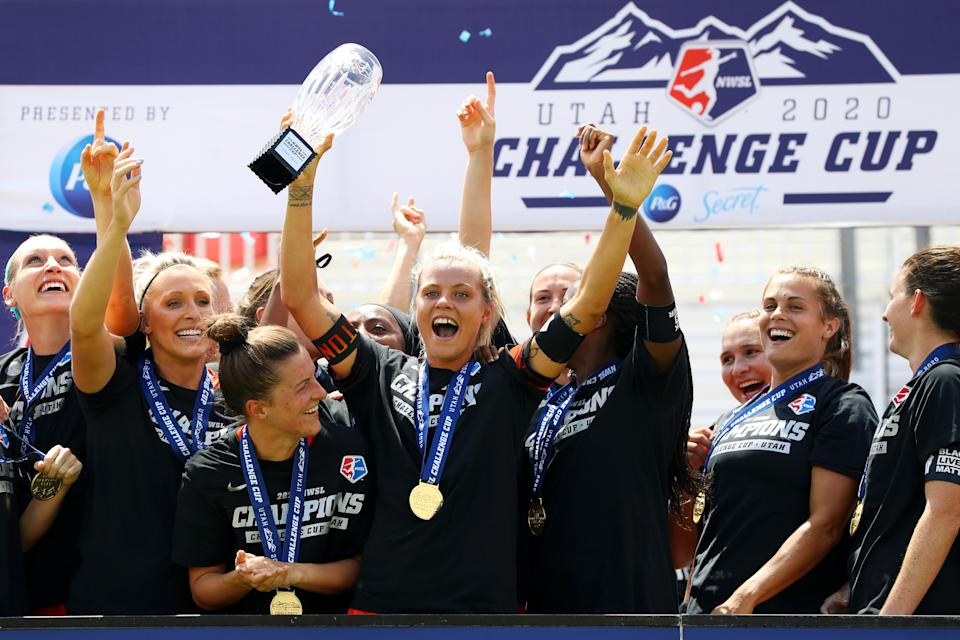 Rachel Daly holds up the NWSL Challenge Cup trophy with her teammates.