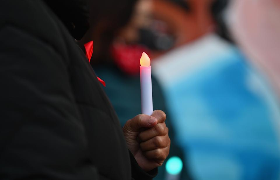 A woman holds a candle in commemoration of World AIDS Day and Covid-19 deaths at NYC Health + Hospitals/Woodhull, on December 1, 2020 in New York City. (Photo by Angela Weiss / AFP) (Photo by ANGELA WEISS/AFP via Getty Images)