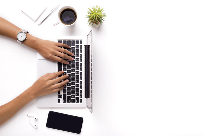 Woman typing on laptop on clean white office table with plant and cup of coffee, copy space