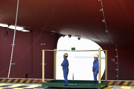 Workers stand in front of a 380,000 DWT class Very Large Ore Carrier (VLOC) during the naming ceremony of two Valemax ships built by Rongsheng Heavy Industries in Nantong, Jiangsu province, in this May 21, 2012 file photo. REUTERS/Aly Song/Files