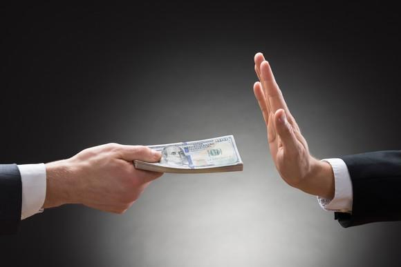 A hand refusing a stack of $100 bills from someone else.