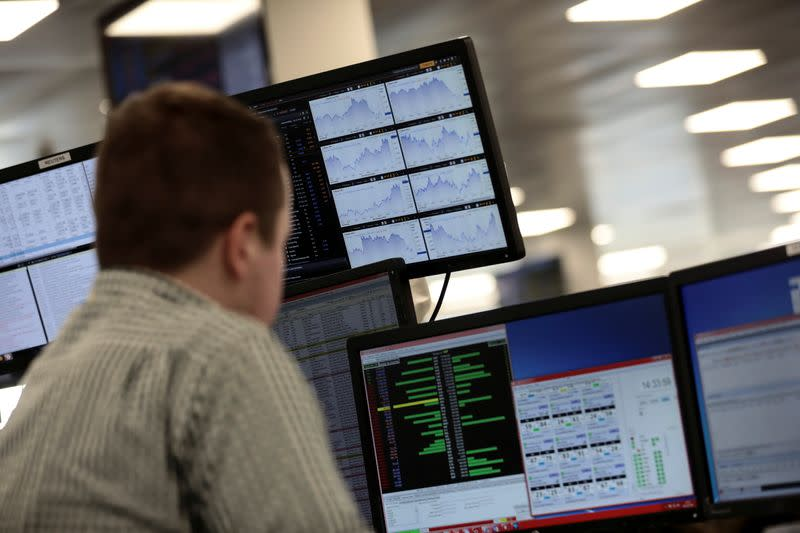 Traders looks at financial information on computer screens on the IG Index trading floor