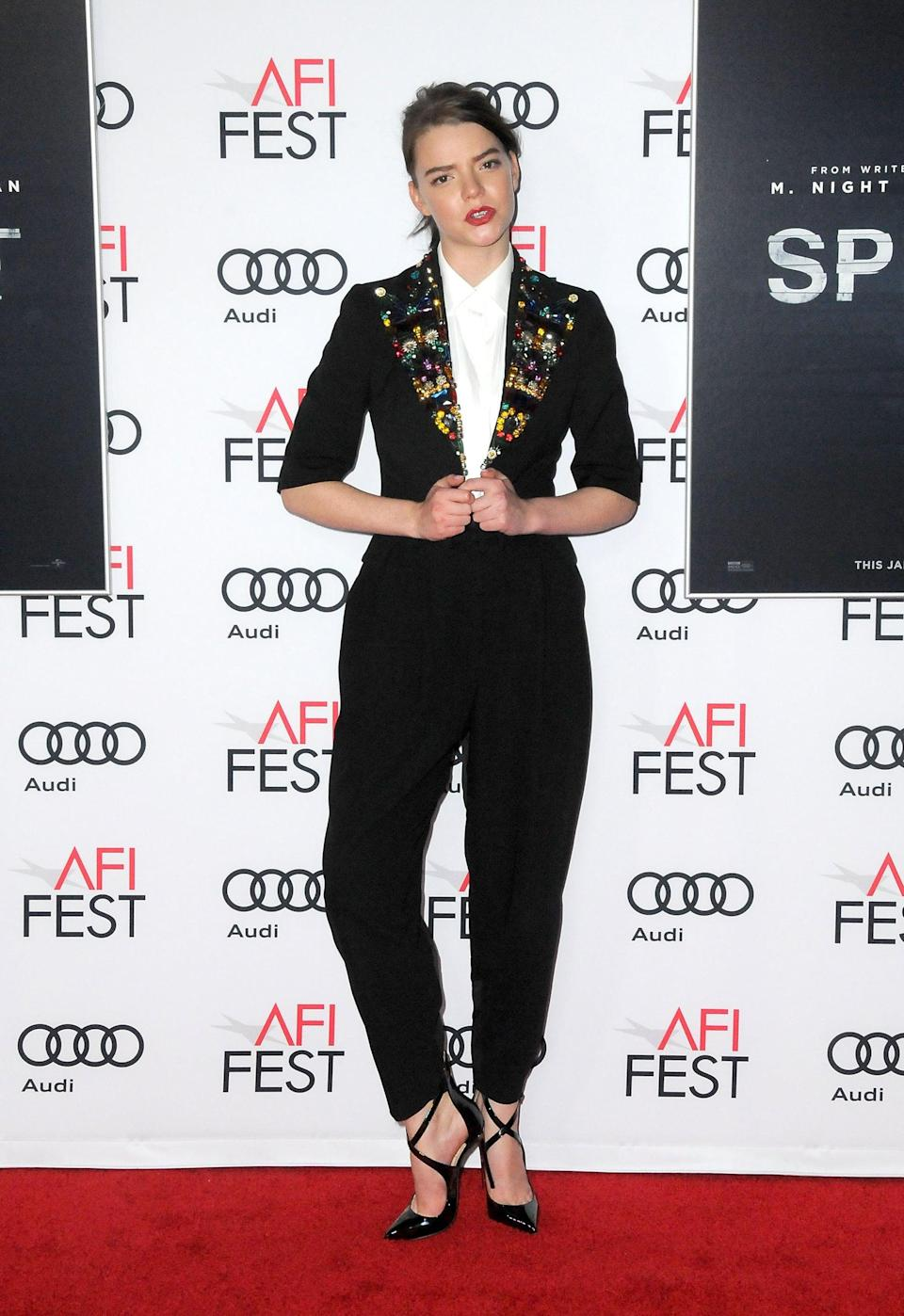 <p>Anya suited up in an embellished jacket, black trousers, and crossover strap shoes.</p>
