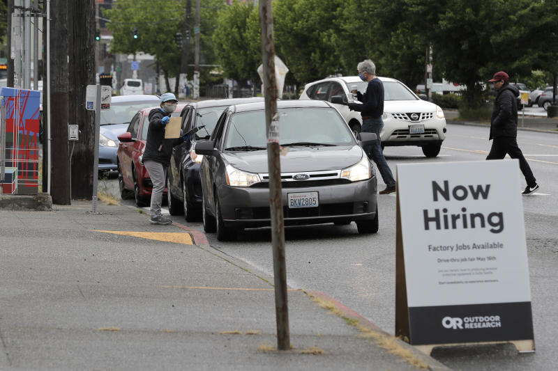 A worker gives instructions to people waiting in cars, Saturday, May 16, 2020, during a walk- and drive-up job hiring fair in Seattle for the Outdoor Research's new line of face masks and other personal protection equipment the outdoor clothing maker has started manufacturing due to the coronavirus pandemic. OR managers were conducting job interviews on the spot and trying to fill about 150 positions related to the company's new line of PPE products. (AP Photo/Ted S. Warren)