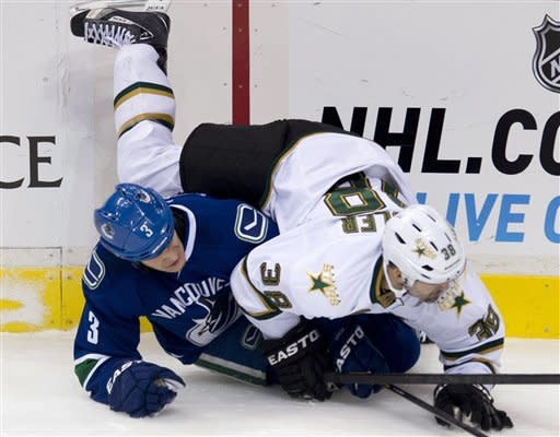 Vancouver Canucks defenseman Kevin Bieksa (3) and Dallas Stars center Vernon Fiddler (38) crash to the ice during the first period of an NHL hockey game in Vancouver, British Columbia, Friday, Feb. 15, 2013. (AP Photo/The Canadian Press, Jonathan Hayward)