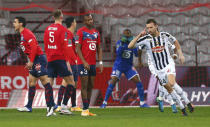 Angers' Romain Thomas, right, celebrates after scoring his side's opening goal during the French League One soccer match between Lille and Angers at the Pierre Mauroy stadium in Villeneuve d'Ascq, northern France, Wednesday, Jan. 6, 2021. (AP Photo/Michel Spingler)