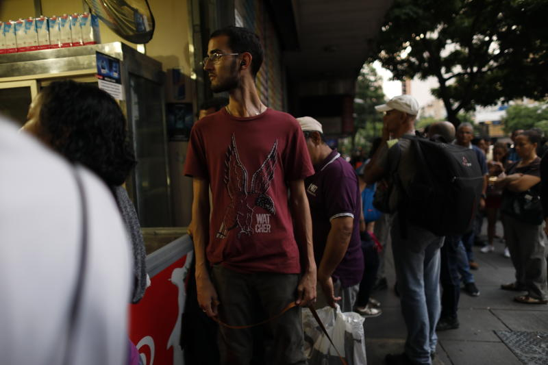 People walk in the streets of Caracas after a massive blackout left the city and other parts of the country without electricity, in Caracas Venezuela, Monday, July 22, 2019. The power in the capital went out around 4:30 p.m. (2030 GMT) and immediately backed up traffic as the subway stopped working and office workers had to begin trekking home during rush hour. (AP Photo/Ariana Cubillos)