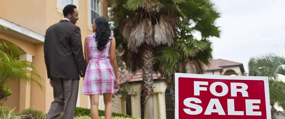 A happy African American man and woman couple house hunting outside a large house with a For Sale sign. The focus is on the sign.