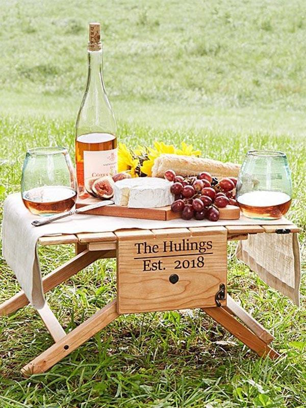 """If you're looking for personalized engagement gifts, Uncommon Goods is a great place to start. We're digging this foldable picnic table-tote hybrid, which can be engraved with a family name and date. $180, Uncommon Goods. <a href=""""https://www.uncommongoods.com/product/personalized-picnic-table-wine-carrier"""" rel=""""nofollow noopener"""" target=""""_blank"""" data-ylk=""""slk:Get it now!"""" class=""""link rapid-noclick-resp"""">Get it now!</a>"""