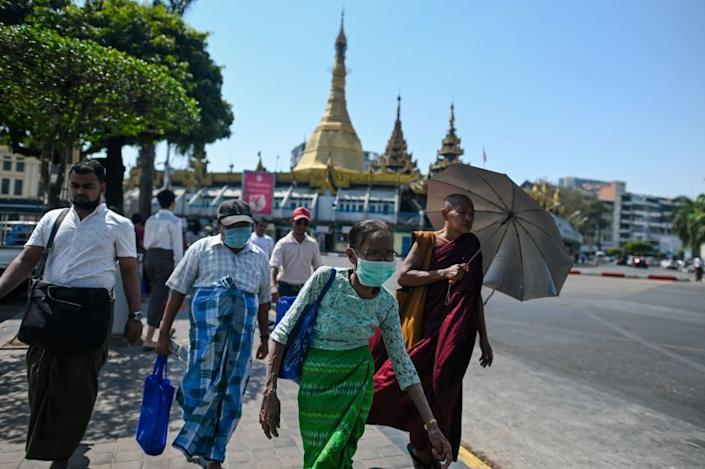 People wearing facemasks amid concerns over the spread of the COVID-19 coronavirus walk to a bus stop in Yangon on March 24, 2020. - Myanmar confirmed its first cases of of the deadly novel coronavirus late March 23 after weeks of increasing scepticism over the under-developed southeast Asian nation's claims to be free of the disease. (Photo by Ye Aung THU / AFP) (Photo by YE AUNG THU/AFP via Getty Images)