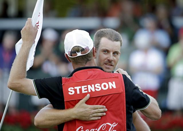 Henrik Stenson, right, of Sweden, embraces his caddie Gareth Lord after sinking a putt to win the Tour Championship golf tournament and FedEx Cup at East Lake Golf Club, in Atlanta, Sunday, Sept. 22, 2013. (AP Photo/David Goldman)