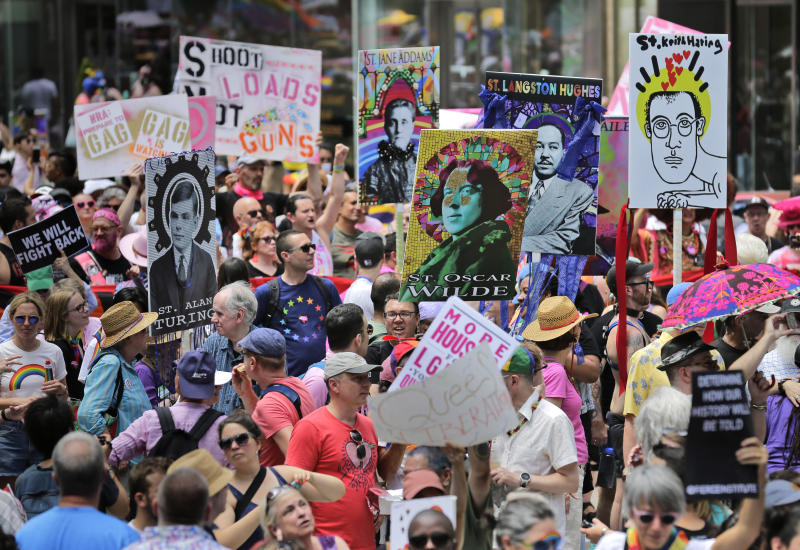 FILE - In this June 30, 2019, file photo, marchers carry signs with historical LGBTQ figures during the Queer Liberation March in New York. This year's Pride events were supposed to be a blowout as LGBTQ people the world over marked the 50th anniversary of the first parade to celebrate what were then the initial small steps in their ability to live openly, and to advocate for bigger victories. Now, Pride is largely taking a backseat, having been driven to the internet by the coronavirus pandemic and now by calls for racial equality that were renewed by the killing of George Floyd in Minneapolis at the hands of police. (AP Photo/Seth Wenig, File)