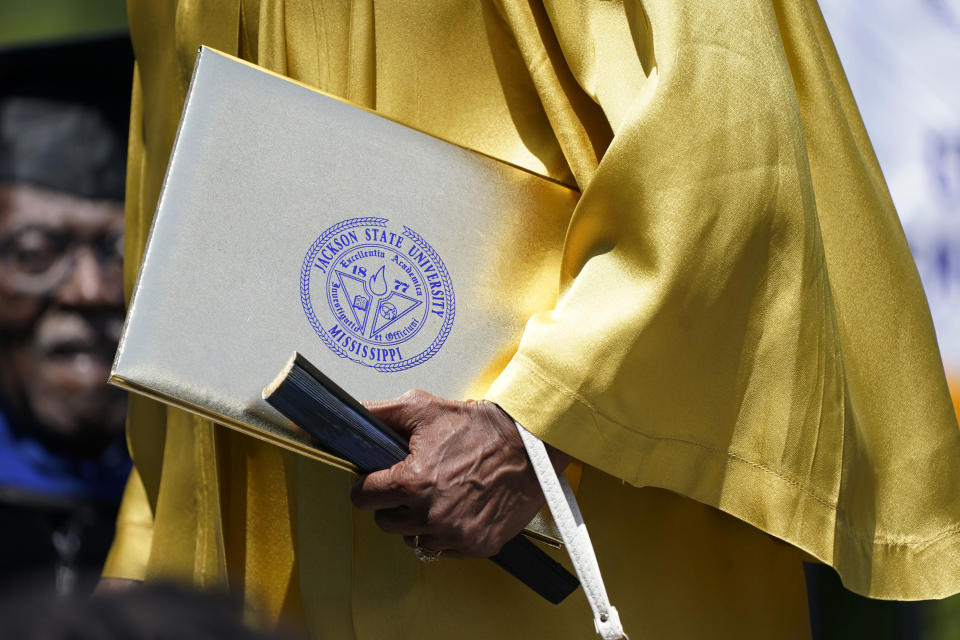 A Jackson State member of the Class of 1970 carries her diploma, as one of 74 graduates honored by the historically Black university with an official graduation ceremony, Saturday, May 15, 2021, in Jackson, Miss. The ceremony was held 51 years after the school canceled its 1970 graduation ceremony after white law enforcement officers marched onto campus near the end of the spring semester and violently suppressed protests against racism with gunfire, killing two and wounding 12. (AP Photo/Rogelio V. Solis)