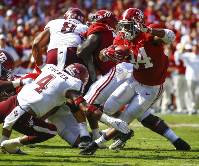 Alabama running back Damien Harris (34) eludes the arms of Texas A&M defensive back Derrick Tucker (4) and carries for first down during the first half of an NCAA college football game, Saturday, Sept. 22, 2018, in Tuscaloosa, Ala. (AP Photo/Butch Dill)