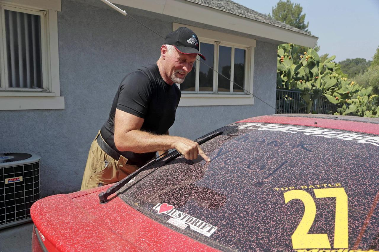 """Lane Leavitt, who trains stunt actors and specializes in setting people on fire for movies and television, writes """"thank you"""" to first responders in red fire retardant that covers his car Tuesday, July 26, 2016, at his home that escaped damage when the Sand fire swept through Santa Clarita, Calif. over the weekend. The fire destroyed 18 homes and authorities said that by Tuesday it had burned more than 37,000 acres, about 58 square miles. (AP Photo/Nick Ut)"""