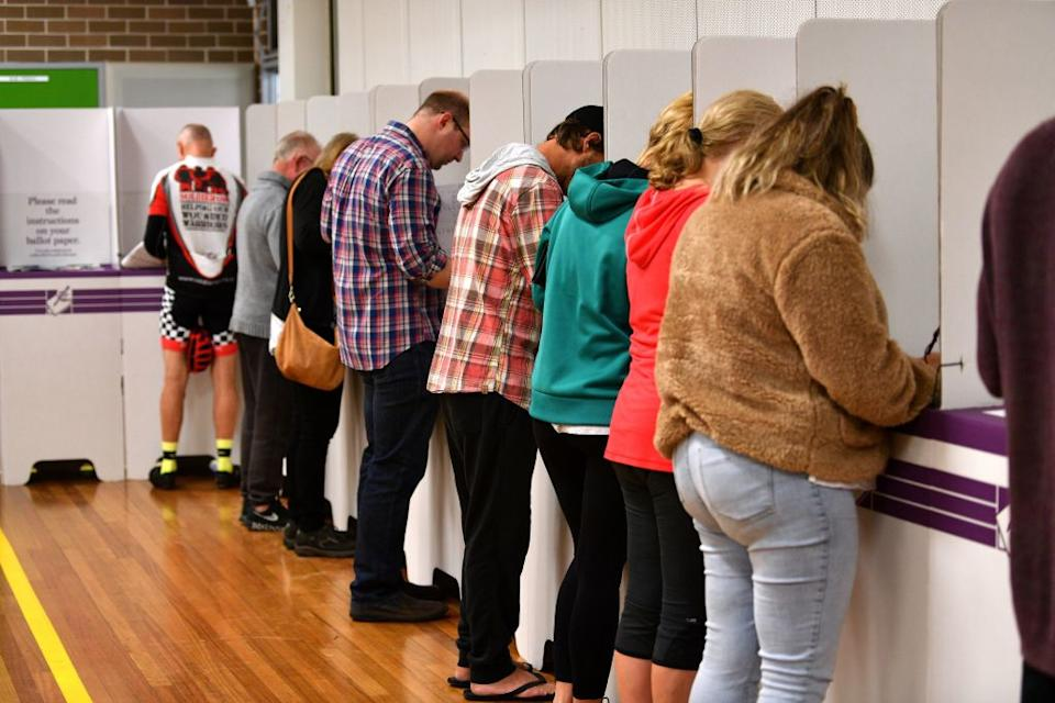 people casting votes in booths
