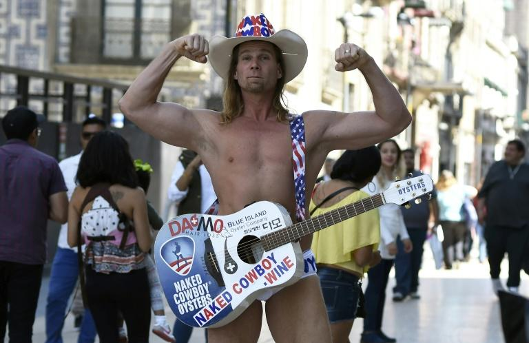 Robert John Burck, an American street performer known as the Naked Cowboy, is seen during a visit to Madero street in Mexico City, where he is singing Trump's praises