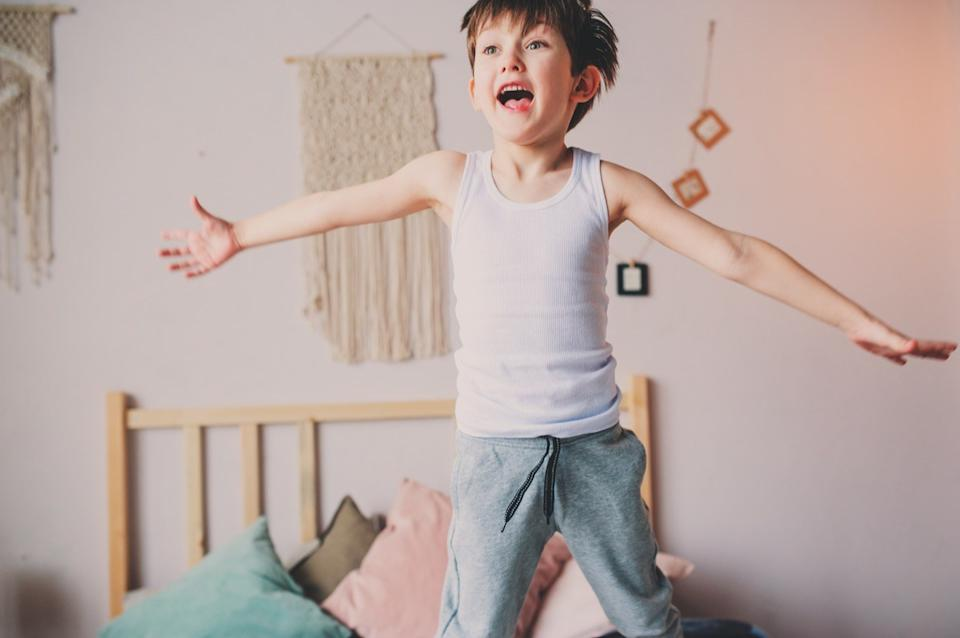 boy jumping on bed in the morning.