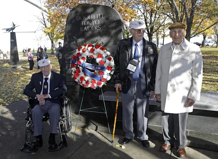 Three of the four surviving members of the 1942 Tokyo raid led by Lt. Col. Jimmy Doolittle, left to right, David Thatcher, Edward Saylor, and Richard Cole, pose next to a monument marking the raid, Saturday, Nov. 9, 2013, outside the National Museum for the US Air Force in Dayton, Ohio. The fourth surviving member, Robert Hite, was unable to travel to the ceremonies. (AP Photo/Al Behrman)