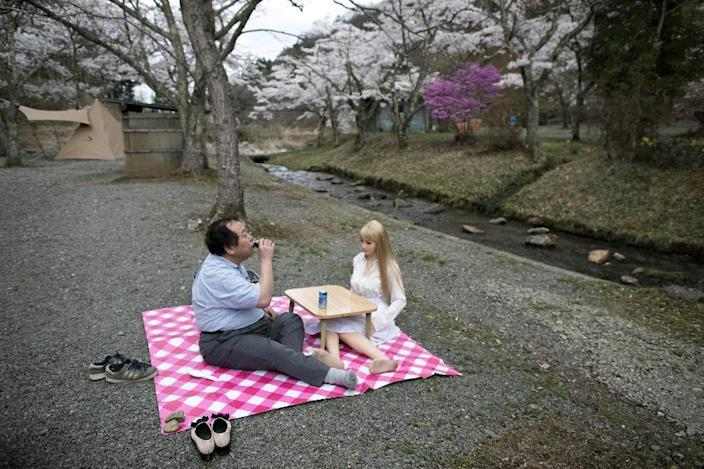 """""""My heart flutters when I come home to Saori,"""" says Senji Nakajima, a married father-of-two as he picnicked with his plastic partner. (AFP Photo/Behrouz MEHRI)"""
