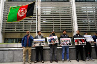 Afghanistan interpreters hold placards and an Afghanistan flag and protest outside the British Government's Home Office in London, Monday, Aug. 23, 2021. Britain is urging the United States to extend its evacuation effort in Kabul beyond the current Aug. 31 deadline, saying without the Americans other countries will have no choice but to stop their own operations to help people fleeing the Taliban takeover. (AP Photo/Alberto Pezzali)