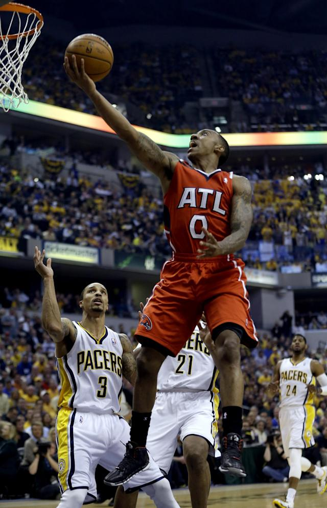 Atlanta Hawks' Jeff Teague (0) goes up for a shot as Indiana Pacers' George Hill (3) defends during the first half in Game 5 of an opening-round NBA basketball playoff series Monday, April 28, 2014, in Indianapolis. (AP Photo/Darron Cummings)