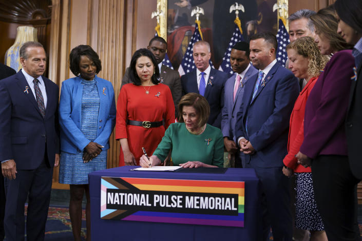 House Speaker Nancy Pelosi, D-Calif., joined by, from left, Rep. David Cicilline, D-R.I., Rep. Val Demings, D-Fla., Rep. Stephanie Murphy, D-Fla., Speaker Pelosi, Rep. Darren Soto, D-Fla., and Rep. Debbie Wasserman Schultz, D-Fla., signs the bill to create the National Pulse Memorial to honor the victims of the 2016 mass shooting at the Pulse nightclub in Orlando, at the Capitol in Washington, Wednesday, June 16, 2021. The shooting was the deadliest attack on the LGBTQ community in U.S. history and left 49 people dead. (AP Photo/J. Scott Applewhite)
