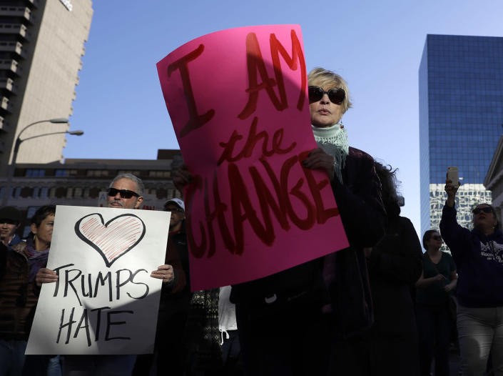 <p>Protesters hold signs as they march in opposition to the election of President-elect, Donald Trump Sunday, Nov. 13, 2016, in St. Louis. (AP Photo/Jeff Roberson) </p>