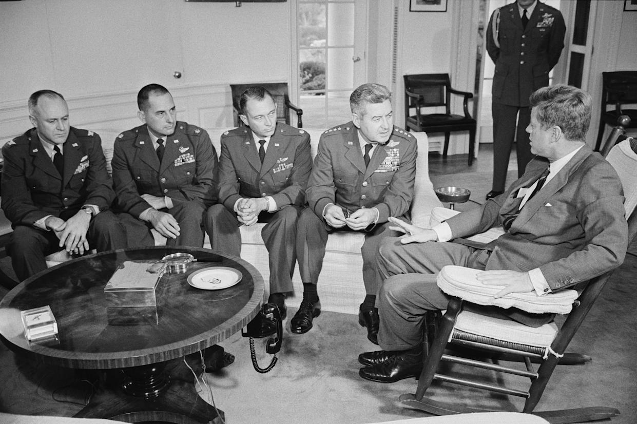 Kennedy (right) meets with and commends two Air Force pilots who had flown reconnaissance missions over Cuba and with the Pentagon officer in charge of evaluating their reports and photographs. From left: Col. Ralph D. Steakley, the evaluator; Lt. Col. Joe M. O'Grady, Amarillo, Texas; Maj. Richard S. Heyser, Apalachicola, Fla.; Gen. Curtis Lemay, Air Force chief of staff, who brought the officers to the White House. (Photo: Bettmann Archive via Getty Images)