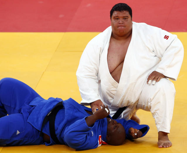 Guam's Ricardo Blas Jr. (R) looks up after winning his men's 100kg elimination round of 32 judo match against Guinea's Facinet Keita at the London 2012 Olympic Games August 3, 2012. REUTERS/Darren Staples (BRITAIN - Tags: SPORT OLYMPICS SPORT JUDO)