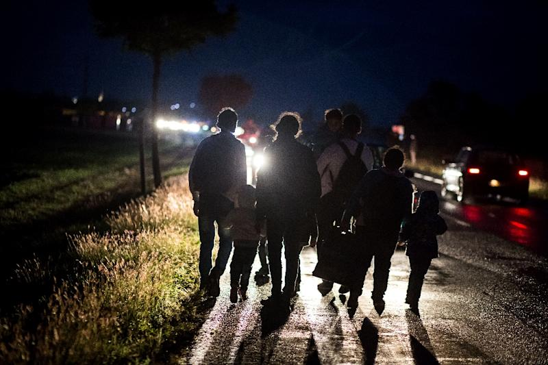 A migrant family walks in the rain towards Nickelsdorf after crossing the Hungarian-Austrian on September 14, 2015 (AFP Photo/Vladimir Simicek)