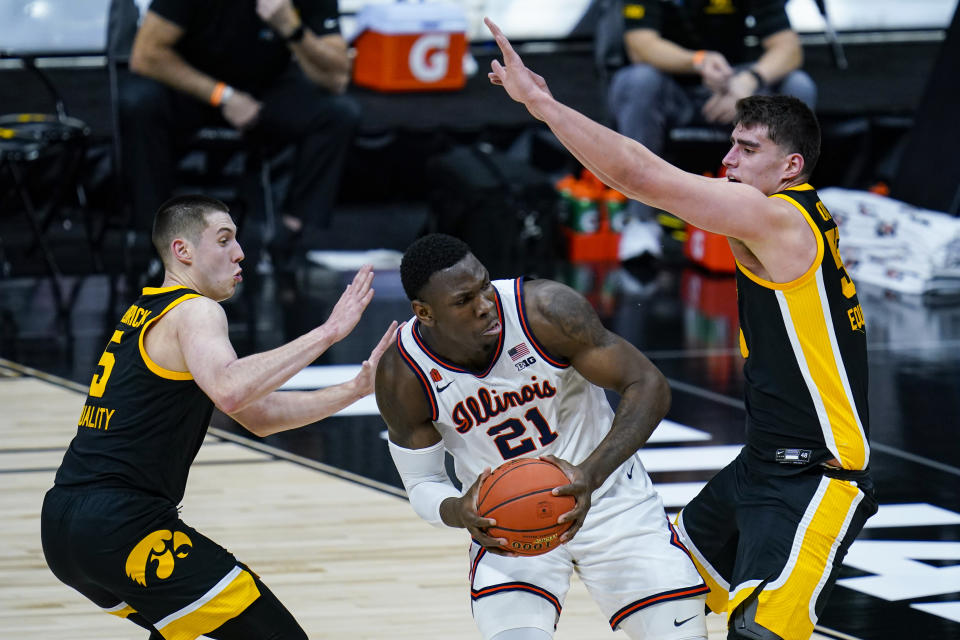 Illinois center Kofi Cockburn (21) looks to shoot between Iowa guard CJ Fredrick (5) and center Luka Garza (55) in the first half of an NCAA college basketball game at the Big Ten Conference tournament in Indianapolis, Saturday, March 13, 2021. (AP Photo/Michael Conroy)