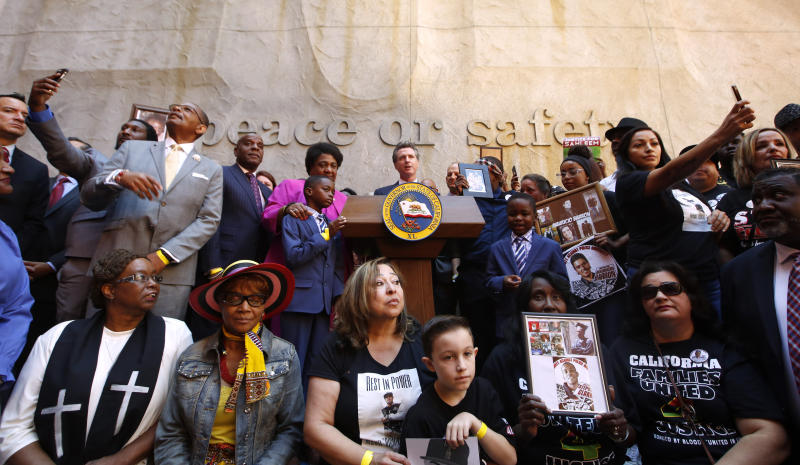 Supporters of a bill limiting the police use of deadly force surround Gov. Gavin Newsom, center, during a signing ceremony in Sacramento, Calif., Monday, Aug. 19, 2019. California is changing its standards for when police can kill under a law signed Monday by Newsom, as it tries to deter police shootings of young minority men that have roiled the nation. (AP Photo/Rich Pedroncelli)