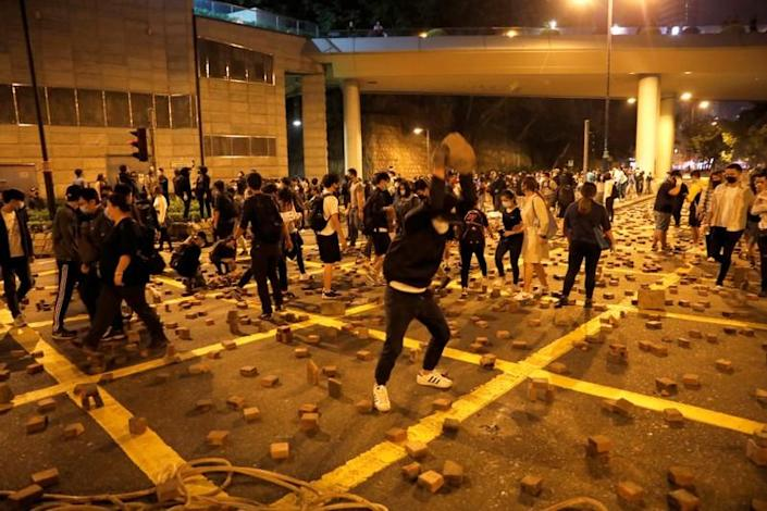 An anti-government demonstrator throws a stone as they block a road near the Hong Kong Polytechnic University (PolyU) in Hong Kong