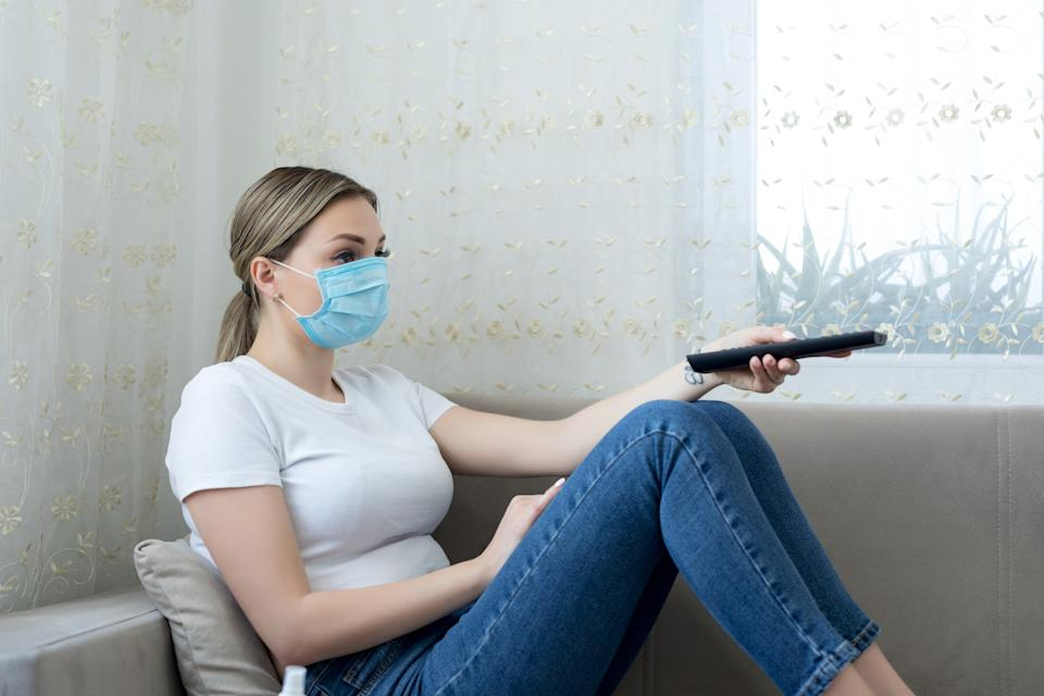 Quarantined woman wearing protective mask watching tv in the living room