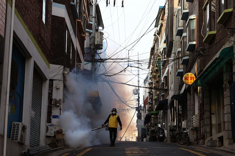A South Korean man in Seoul disinfects an alley to prevent the spread of coronavirus, March 18, 2020. (Photo: Chung Sung-Jun via Getty Images)