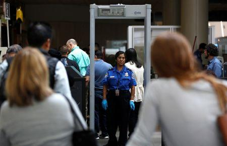 Travelers stand in line to go through Transportation Security Administration (TSA) check-points at Los Angeles International Airport in Los Angeles