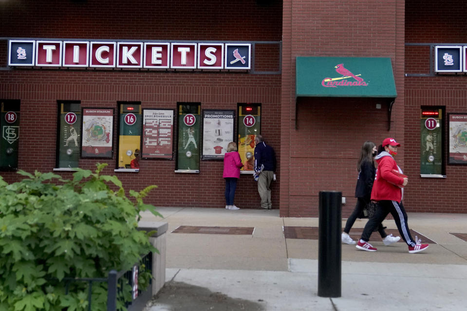 People walk outside Busch Stadium after the start of a baseball game between the St. Louis Cardinals and the New York Mets was delayed because of rain Tuesday, May 4, 2021, in St. Louis. (AP Photo/Jeff Roberson)