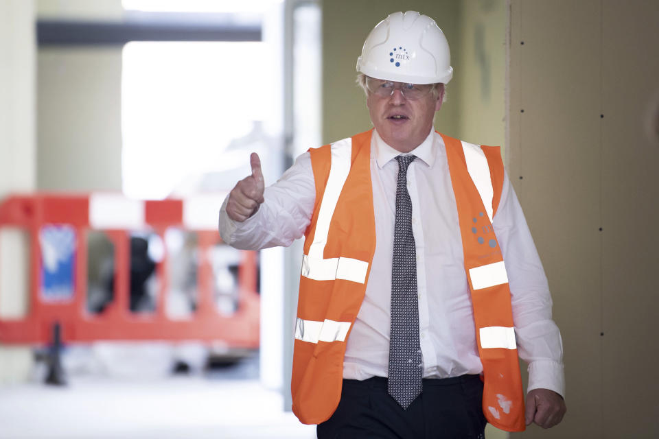 Britain's Prime Minister Boris Johnson, gestures, during a visit to a construction site, in Hereford, England, Tuesday, Aug. 11, 2020. Hereford County Hospital is expanding with a three storey modular building providing 72 new beds over three wards under construction. The new facility will open early 2021. (Matthew Horwood/Pool Photo via AP)