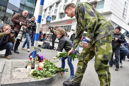 People laying flowers near the crime scene in central Stockholm the morning after a hijacked beer truck plowed into pedestrians