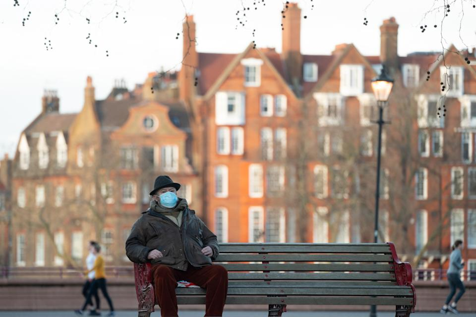 A man wearing a face covering sits on a bench in Battersea Park in London during the third covid lockdown. Photo date: Friday, January 29, 2021. Photo credit should read: Richard Gray/EMPICS