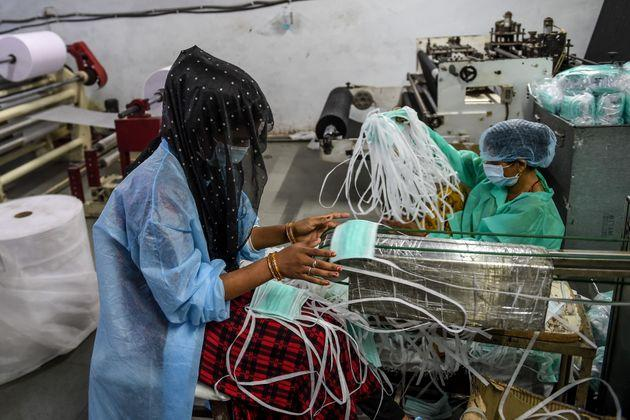 A worker collects facemasks from an assembly line at a facility of personal protective equipments manufacturer Nikshe Multiproducts on the outskirts of Ahmedabad on April 2, 2020.