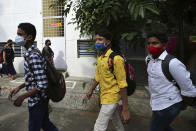 Students wearing face masks as a precaution against the coronavirus arrive to attend classes at a school in Bengaluru, India, Friday, Jan. 1, 2021. The southern state of Karnataka on Friday opened schools for the students of grade 10 and 12 after a gap of more than nine months. India has more than 10 million cases of coronavirus, second behind the United States. (AP Photo/Aijaz Rahi)
