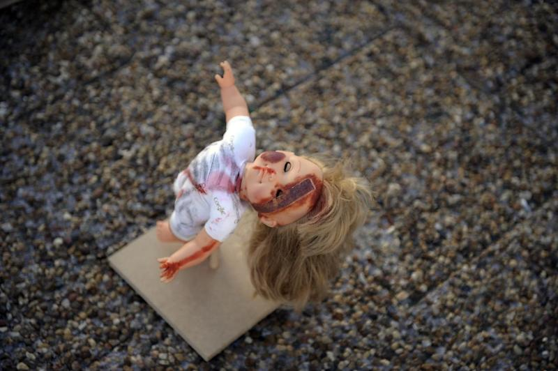 A beaten-up and bruised doll on display in Tel Aviv as part of an exhibition to raise public awareness of child abuse (AFP Photo/David Buimovitch)