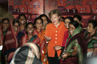 FILE - In this Wednesday, Oct. 31, 2007, file photo, German Chancellor Angela Merkel, center, asks a woman, front, to join a group photo with Indian country women during her visit to the NABARD-Bank in Mumbai, India. On trips to Africa, the Middle East and Asia, Merkel has often made a point of visiting women's rights projects. She has always stressed that giving women in poor countries better access to education and work is key to those nations' development. (AP Photo/Herbert Knosowski, File)