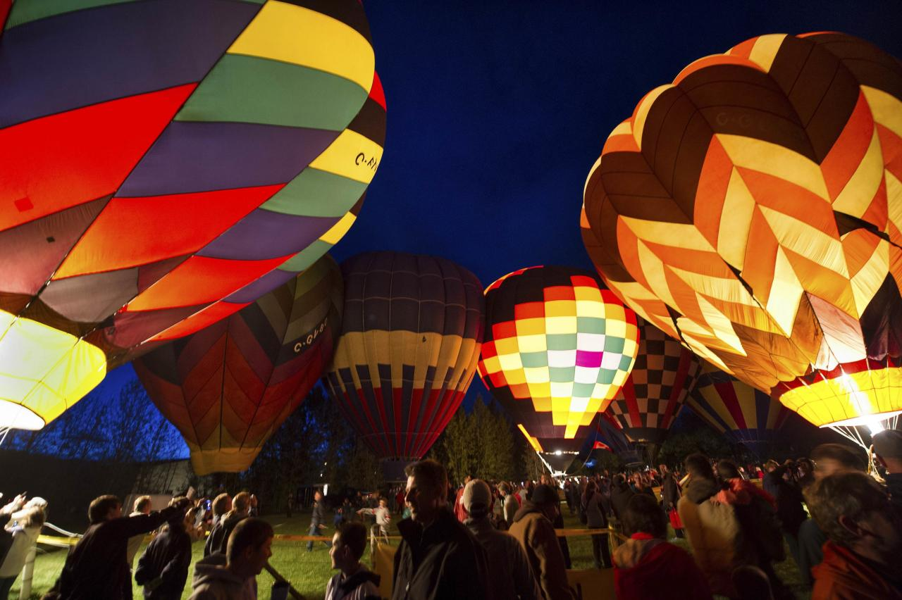 People look at hot air balloons during a night glow on the evening of Day 3 of the Canadian Hot Air Balloon Championships in High River
