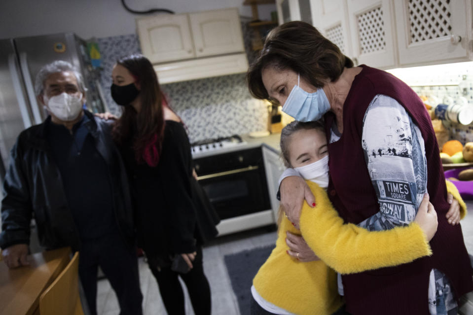 Rita Cintio, 76, wears a face mask to curb the spread of COVID-19 as she hugs at her niece Gaia, while her husband Felice Santini, left, talks with their other niece Elisa, while visiting them at their son's house, in Rome, Wednesday, Dec. 16, 2020. In Italy, which has the world's second-oldest population, many people in their 70s and older have kept working through the COVID-19 pandemic. From neighborhood newsstand dealers to farmers bring crops to market, they are defying stereotypic labels that depict the old as a monolithic category that's fragile and in need of protection. (AP Photo/Alessandra Tarantino)