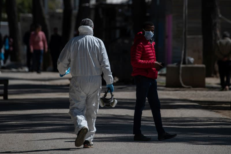 A Health Ministry official wearing a protective suit walks past a migrant wearing a protective face mask and standing in the Ritsona camp, after authorities found 20 coronavirus cases and placed the camp under quarantine, in Ritsona