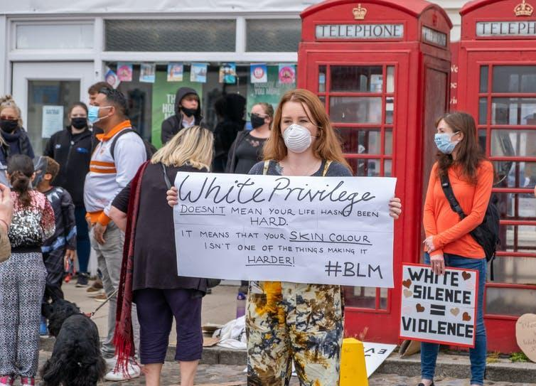 A protester holding up a sign that says 'white privilege doesn't mean your life hasn't been hard, it means your skin colour isn't one of the things making it harder'